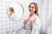 veselá žena v županu s úsměvem v koupelně