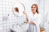 veselá žena v županu s úsměvem při gestikulování v koupelně