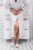 abgeschnittene Ansicht einer Frau im Bademantel, die unter Bauchschmerzen im Badezimmer leidet