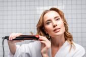 žena v bílém županu pomocí rovnání vlasů v koupelně