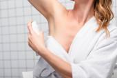 částečný pohled na ženu v bílém ručníku aplikující deodorant v koupelně