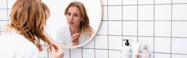 Upset woman in bathrobe adjusting hair while looking at mirror in bathroom, banner stock vector
