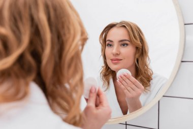 Happy woman applying toner with cotton pad on face and looking at mirror stock vector