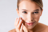 örömteli fiatal nő alkalmazása hidratáló krém az arcon elszigetelt fehér