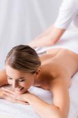 rozmazaný masér úprava ručník na šťastný klient ležící na masážním stole