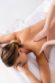 vysoký úhel pohledu masérky masírující záda ženy na masážním stole