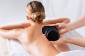 cropped view of masseur holding black hot stones near client in spa salon