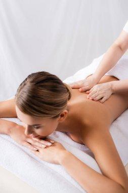 masseur massaging back of client lying on massage table