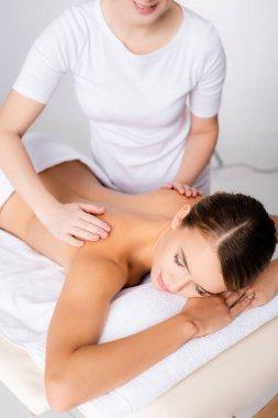 smiling masseur massaging back of client on massage table