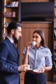 young businesswoman drinking coffee near arabian business partner in restaurant