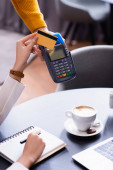 cropped view of freelancer holding credit card near payment terminal un hand of waiter
