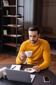junge arabische Freiberuflerin hält eine Tasse Kaffee in der Hand, während sie im Restaurant auf den Laptop schaut