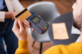 partial view of arabian man hold credit card near payment terminal in hands of waitress