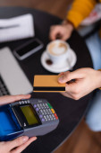 partial view of freelancer holding credit card near payment terminal in hands of waitress, blurred background