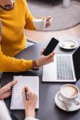 Vágott kilátás az ember mutatja okostelefon üres képernyőn, hogy barátja notebook közelében kávé és laptop az asztalon