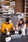 Arab férfi mutatja igen gesztus közelében barátja okostelefon, laptop és kávé étteremben