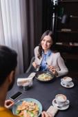 Usmívající se žena při pohledu na přítele u večeře, kávy a smartphone na rozmazané popředí v restauraci