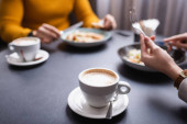 Cropped view of cappuccino near couple dinning in restaurant on blurred background