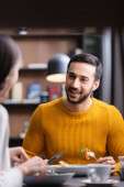 Smiling arabian man looking at girlfriend on blurred foreground while dinning in restaurant