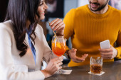 Smiling woman holding cocktail near friend with smartphone on blurred foreground in restaurant