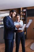 Multietničtí podnikatelé s notebookem a schránkou pracující v restauraci