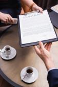 Oříznutý pohled na obchodníka, který bere kontrakt od podnikatelky v blízkosti kávy v restauraci