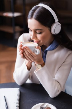 pleased woman in wireless headphones enjoying flavor of coffee while holding cup with closed eyes