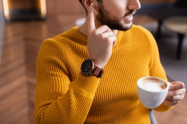 cropped view of arabian man adjusting earphone while holding cup of coffee in restaurant