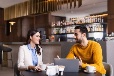 Young arabian freelancer talking to cheerful friend near laptop and coffee cups in restaurant, blurred foreground stock vector