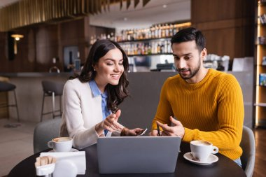 Multiethnic friends looking at laptop near coffee on blurred foreground in restaurant stock vector