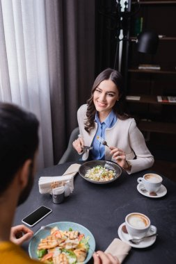 Smiling woman looking at boyfriend near dinner, coffee and smartphone on blurred foreground in restaurant stock vector