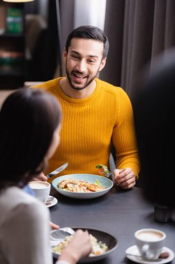 Cheerful arabian man holding cutlery near delicious salad, cappuccino and girlfriend on blurred foreground in restaurant stock vector