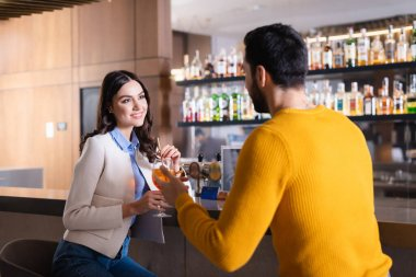 Smiling woman with cocktail looking at muslim friend on blurred foreground near bar counter in restaurant stock vector