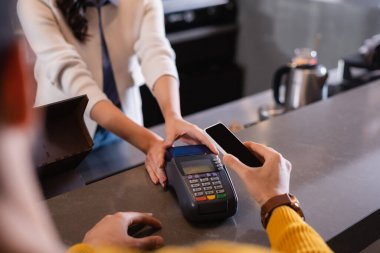 Cropped view of man paying with smartphone near payment terminal in restaurant stock vector
