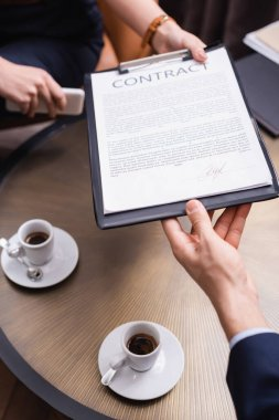Cropped view of businessman taking contract from businesswoman near coffee in restaurant stock vector