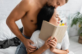 Young woman holding book near sexy boyfriend in bedroom