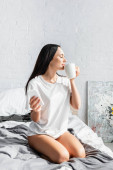 Young woman with cup and smartphone sitting on bed