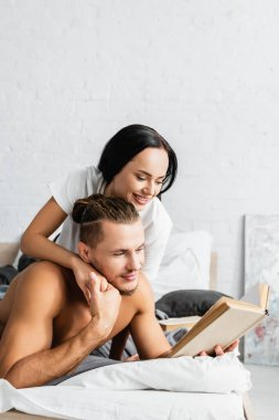 Smiling woman embracing shirtless boyfriend with book on bed stock vector