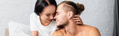 Brunette woman kissing shirtless boyfriend in bedroom, banner stock vector