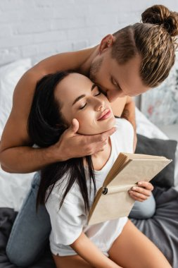 Shirtless man kissing brunette girlfriend with book in bedroom stock vector
