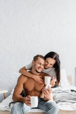 Smiling woman with cup hugging sexy boyfriend with smartphone on bed stock vector