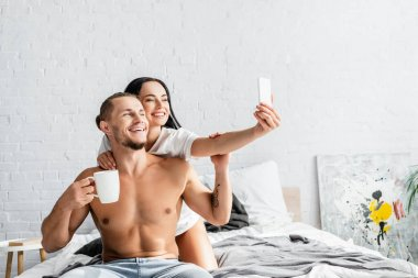 Young woman taking selfie with shirtless boyfriend holding cup on bed stock vector