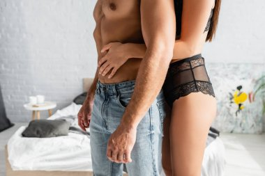 Cropped view of woman in bra and panties touching torso of man in jeans in bedroom stock vector