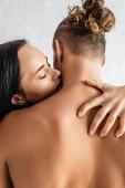 Junge Frau küsst hemdlosen Mann zu Hause