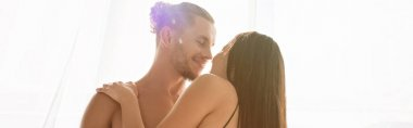 Shirtless man smiling and kissing brunette woman near window, banner