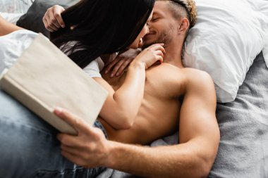 Shirtless man holding book on blurred foreground while kissing girlfriend on bed stock vector