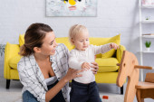 laughing woman supporting toddler standing near rocking horse