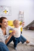 Aufgeregte Frau unterstützt Kleinkind beim Gehen zu Hause