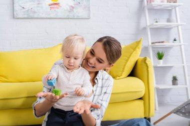 Joyful woman holding toy cube near little son at home stock vector