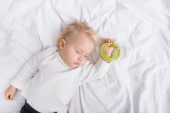top view of toddler sleeping with rattle on white bedding at home